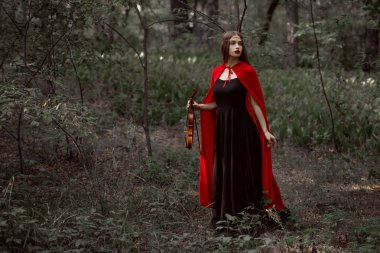 beautiful mystic girl in black dress and red cloak holding violin in forest