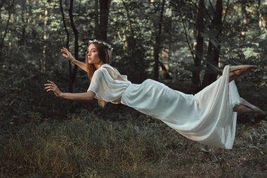 Elegant beautiful girl in white dress flying in forest stock vector