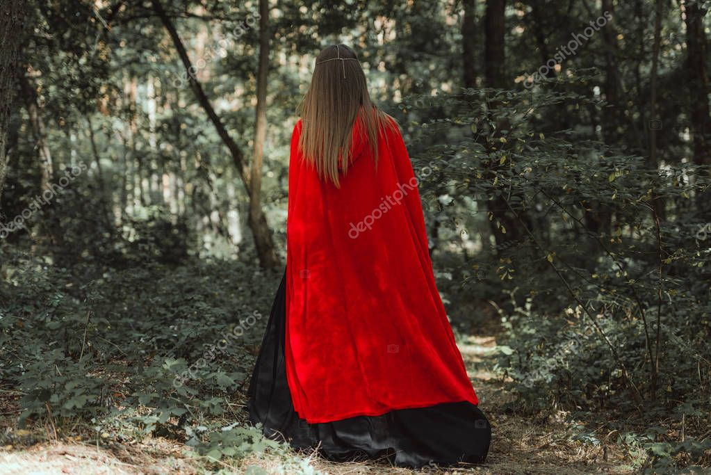 back view of mystic woman in red cloak in forest