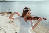 attractive young woman in elegant dress and floral wreath playing violin on seashore