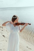 beautiful woman in elegant white dress and floral wreath playing violin on seashore