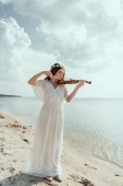Fotografie beautiful elegant girl in white dress and floral wreath playing violin on sand beach