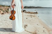 Photo cropped view of elegant girl in white dress holding violin on sand beach