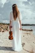 Fényképek elegáns fehér ruha gazdaság hegedű lány tengerparton hátulnézete