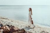 Fényképek beautiful elegant woman in white dress holding violin and walking on beach near sea