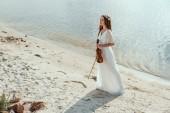 krásná mladá žena v hospodářství housle na písčité pláži elegantní šaty