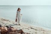 atraktivní mladá žena v elegantních šatech s housle chůzi na pláži u moře