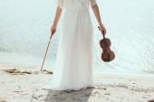 Fényképek gazdaság hegedű tengerpart fehér ruha lány levágott megtekintése