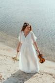 Fényképek elegant attractive girl with violin on sea shore