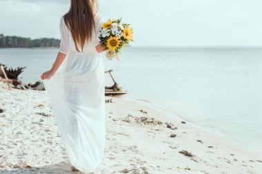 rear view of woman in white dress holding bouquet with sunflowers on beach