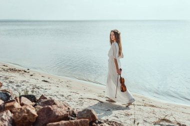 beautiful elegant woman in white dress holding violin and walking on beach near sea