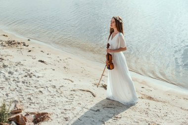 beautiful young woman in elegant dress holding violin on sand beach