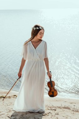 beautiful elegant woman in dress and floral wreath holding violin on beach near sea