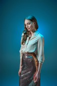 krásná žena v módní zlaté třpytivé sukni při pohledu na fotoaparát izolované na modré