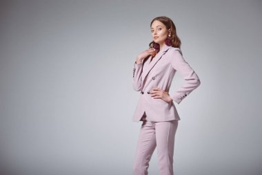 beautiful woman in stylish pink suit posing with hand on waist and looking at camera isolated on grey