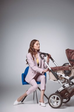 beautiful fashionable woman sitting on chair and looking at baby carriage on grey