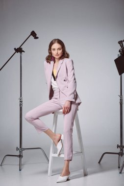 fashionable woman sitting on stool and looking at camera in recording studio