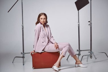 Fashionable woman in pink suit sitting on suitcase and looking at camera in recording studio stock vector