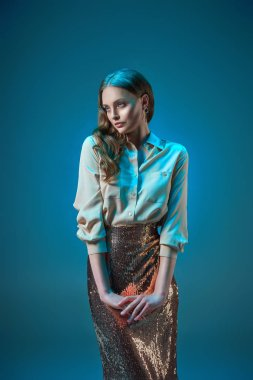 beautiful woman in fashionable golden glittering skirt looking away isolated on blue