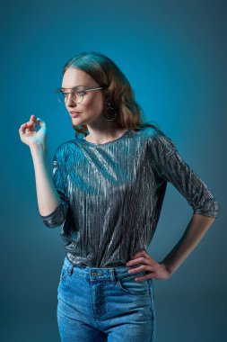 beautiful stylish woman in eyeglasses posing with hand on waist and looking away isolated on blue