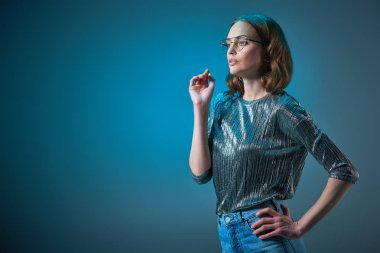 beautiful stylish woman in spectacles posing with hand on waist and looking away isolated on blue
