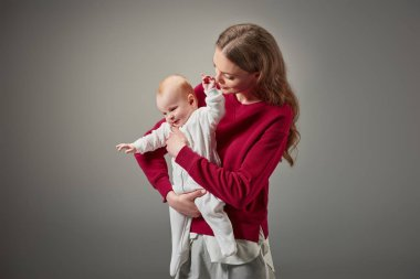 beautiful stylish young mother smiling and looking at adorable infant daughter isolated on grey