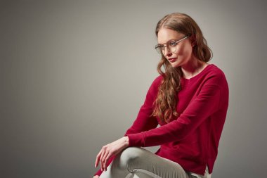 beautiful fashionable woman in eyeglasses sitting and looking away isolated on grey