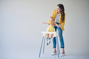 beautiful stylish mother putting baby girl in high chair on grey