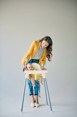 fashionable mother looking at infant sitting in high chair on grey
