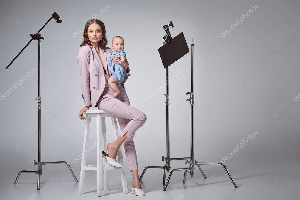 Beautiful stylish mother holding adorable infant daughter and looking at camera while sitting on stool in recording studio stock vector