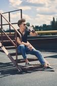 Fotografia uomo alla moda bere rum, seduti sulle scale sul tetto