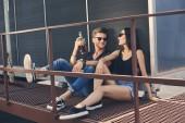 Fotografie asiatische Freundin und kaukasischen Freund mit Flasche Rum, Zeit miteinander zu verbringen, auf Dach