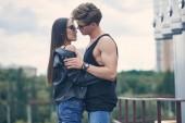 multiethnische heiße paar gehen auf städtischen Dach stehend zu küssen