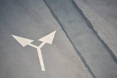 two way arrow symbol on grey asphalt road