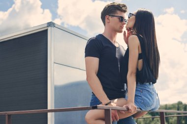 interracial hot couple going to kiss on railings on roof