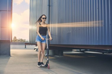 attractive asian girl riding scooter on roof with sunlight