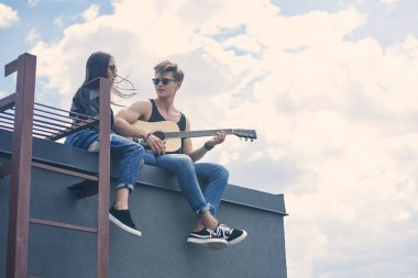 handsome guitarist playing for his attractive asian girlfriend on roof