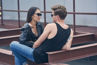 multiethnic stylish sexy couple in sunglasses looking at each other