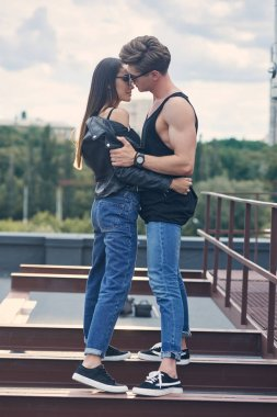 multiethnic stylish hot couple in sunglasses embracing and going to kiss on urban roof