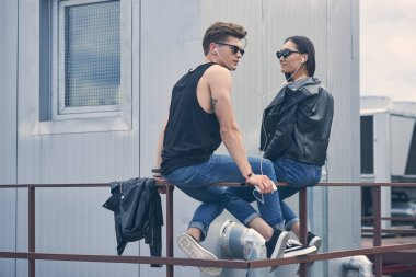 beautiful multicultural couple listening music with earphones while sitting on roof