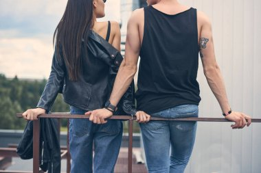 back view of young stylish couple standing near railings on roof