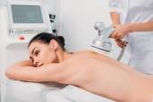 atraktivní žena na masážní stůl dostat elektrického masáž provádí kosmetička v salonu spa