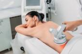 Žena na masážní stůl dostat elektrického masáž provádí kosmetička v salonu spa