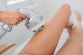 Fotografia ritagliata colpo del cosmetologo fare massaggio elettrico al client femmina in biancheria intima bianca nel salone della stazione termale