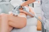 vista parziale del cosmetologo elettrici massaggio al client femmina in biancheria intima bianca nel salone della stazione termale