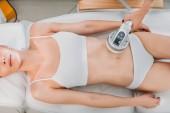 részleges kilátás nyílik a kozmetikus, hogy elektromos masszázs női ügyfél fehér fehérnemű a spa szalon