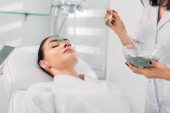Fotografia vista parziale del cosmetologo applicazione maschera di argilla sul fronte femminile nel salone della stazione termale
