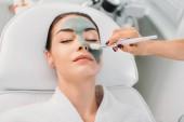 Teilansicht des Kosmetikers, der im Wellness-Salon Tonmaske auf das weibliche Gesicht aufträgt