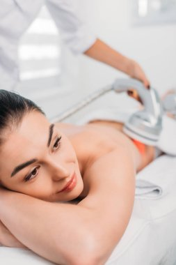 beautiful woman on massage table getting electrical massage done by cosmetologist in spa salon