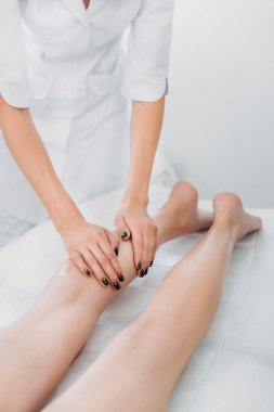 cropped shot of cosmetologist massaging clients legs in spa center
